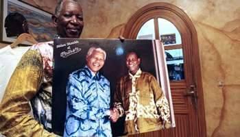 Pathe'O tenant une photo de lui avec Nelson Mandela